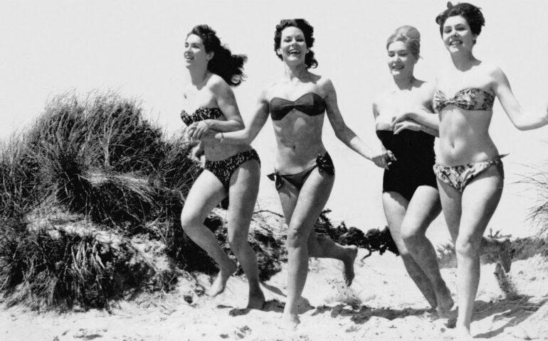 Oude foto van vrouwen die in bikini over het strand rennen