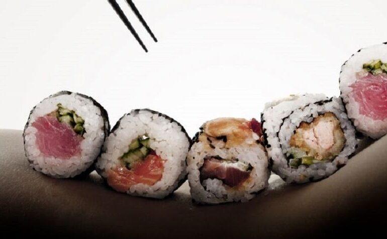 Naakte vrouw met sushi op haar rug