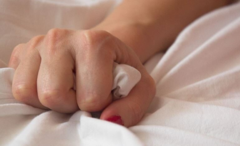 A hand holding the sheets in bed