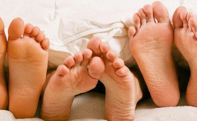 Three pair of feet in bed