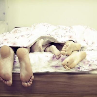 Grote en kleine voeten steken uit bed