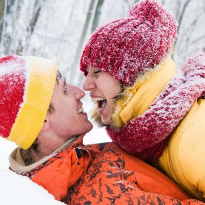 Man en vrouw knuffelen in de sneeuw