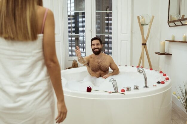 Man in bad met vrouw handdoek om haar lichaam