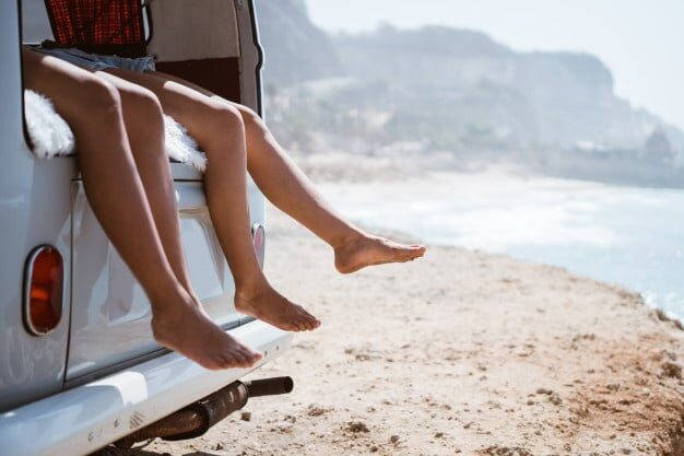 Man and womans legs out of a car