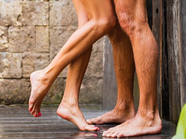 Man and woman under shower outisde