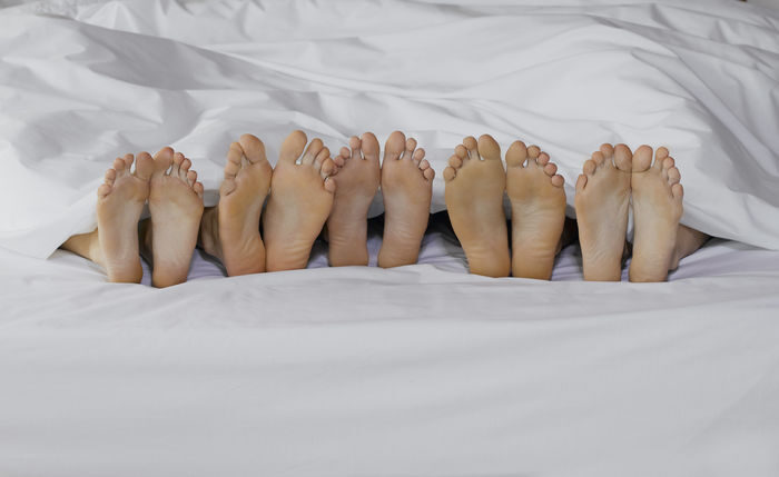 5 pair of feet in a bed