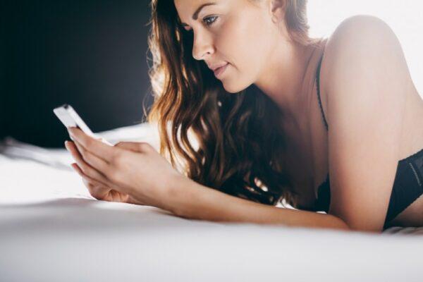 Vrouw op bed met telefoon