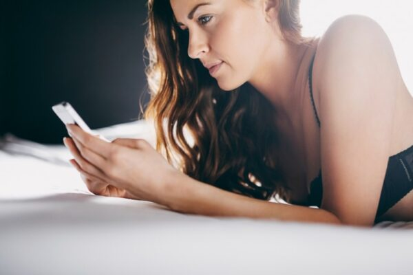Woman on bed with smartphone